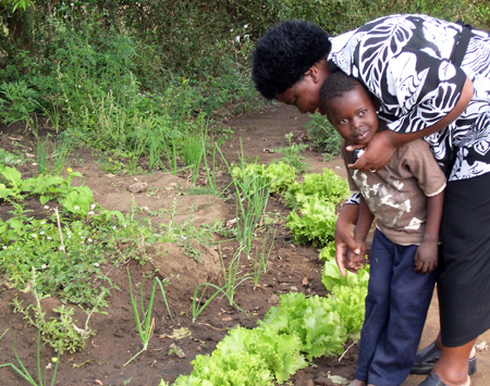 Beauty Masilela showing a child the first self-grown spinage